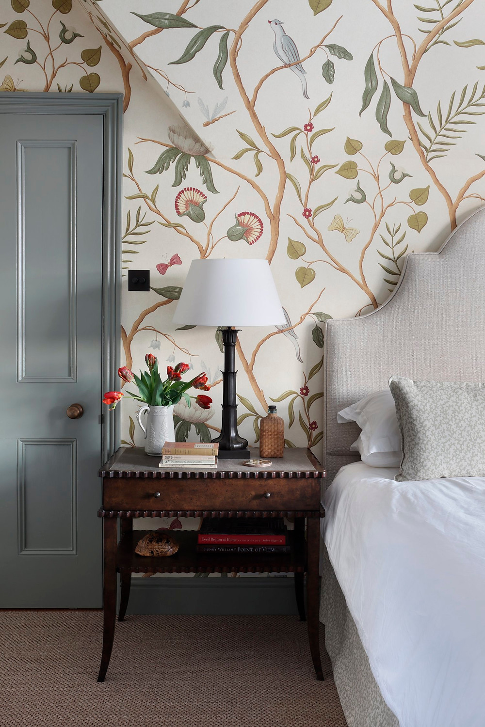 bedroom with wallpaper and upholstered headboard