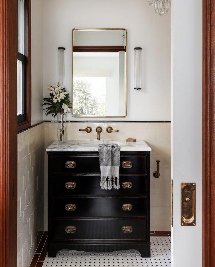 bathroom with basketweave tile and black vanity