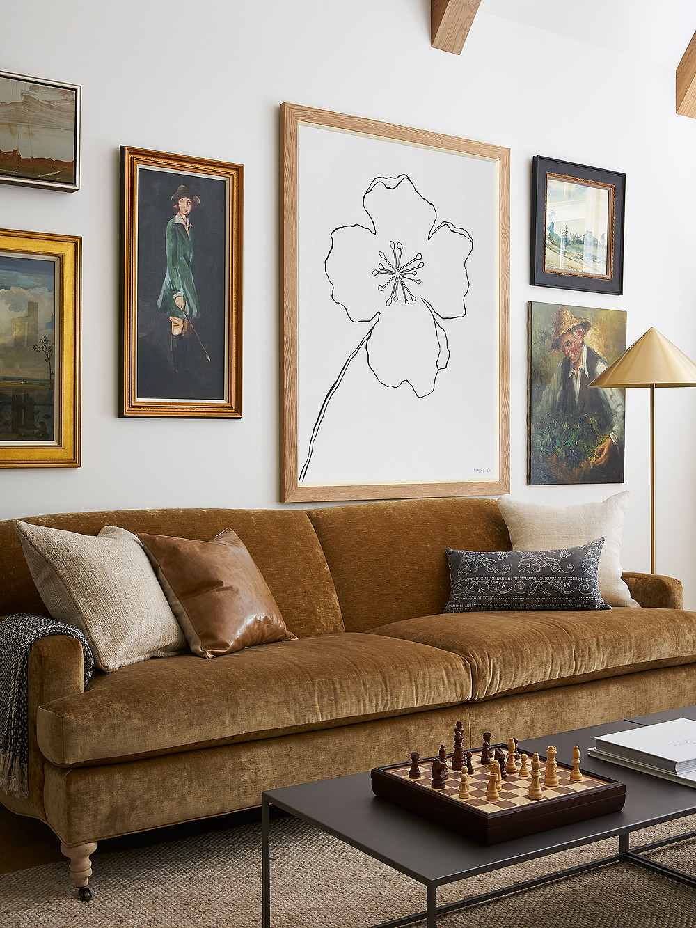brown velvet sofa with gallery wall