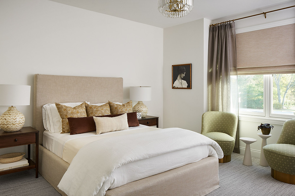 bedroom with upholstered bed and green chairs