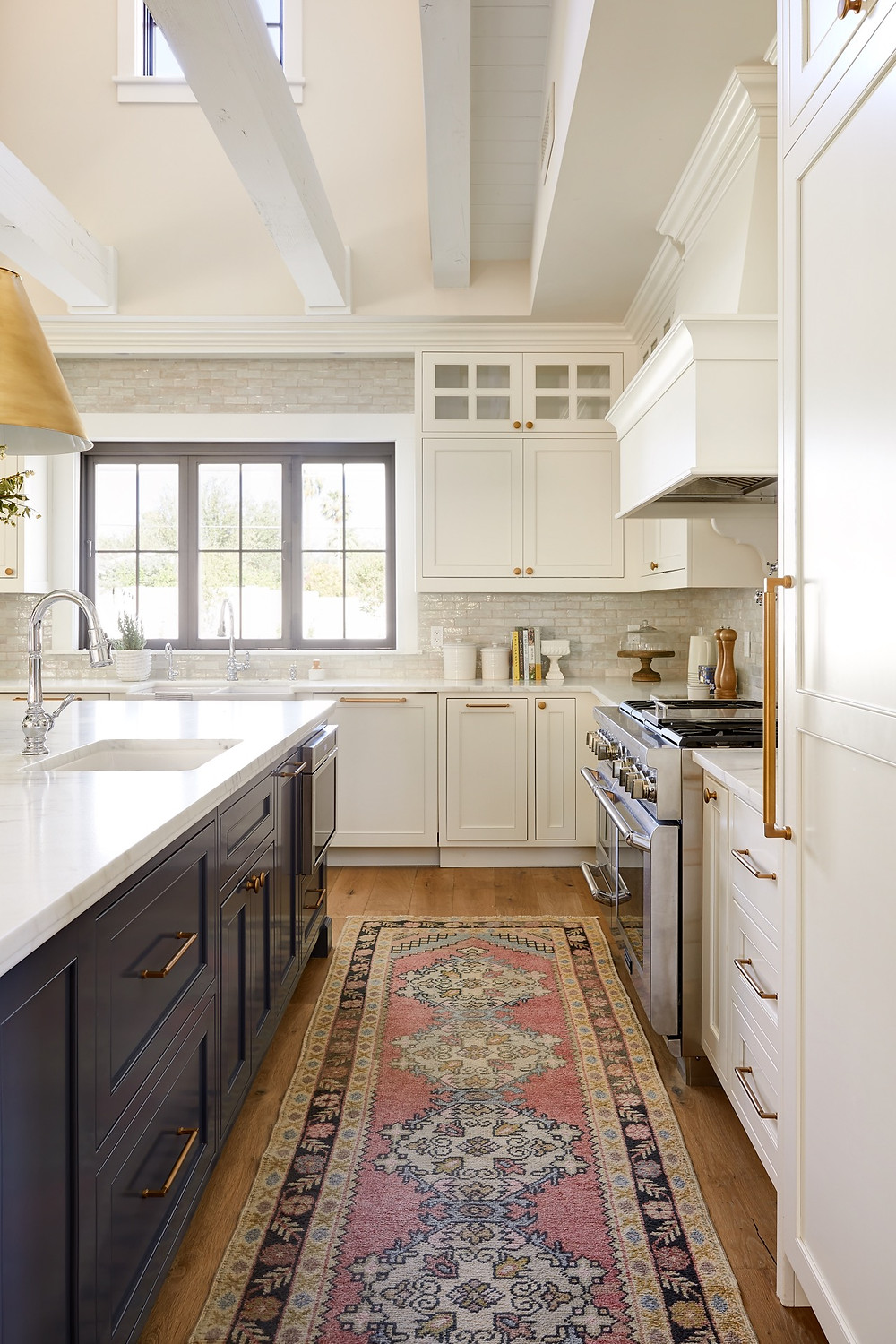 The difference between a full furnishing project and a remodel or new construction project. Bright and airy transitional kitchen with white cabinets and dark island with oversized brass pendant lights designed by Lexi Westergard Design.