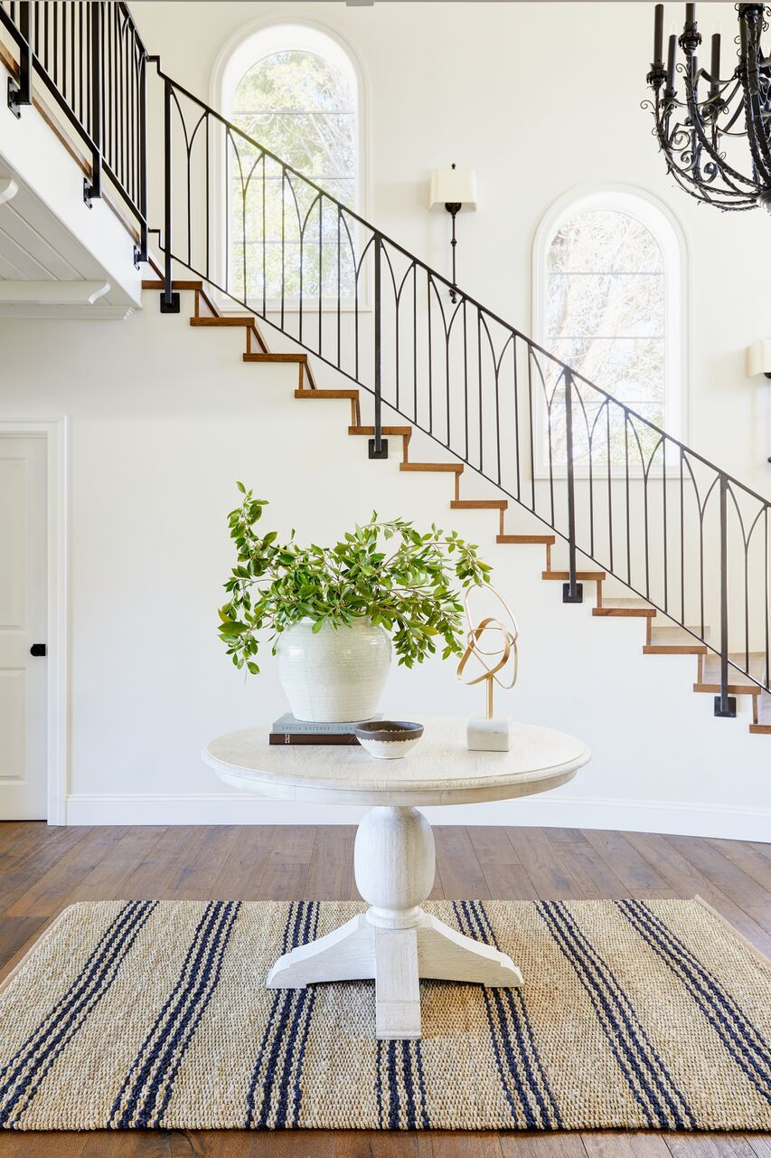 The difference between a full furnishing project and a remodel or new construction project. Bright and airy  grand entry with striped rug, round wood table and oversized fresh greenery designed by Lexi Westergard Design.