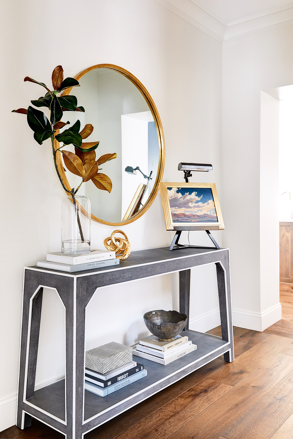 Bright and airy transitional hallway design with round gold mirror and  styled console table featuring an art stand. Click through for the 7th Avenue Project reveal by Phoenix based interior designer, Lexi Westergard Design.