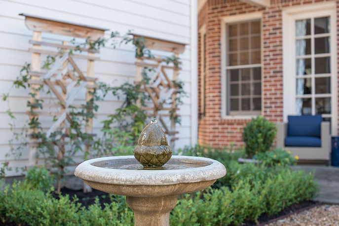 This transformation was our first foray into exterior design. We started with a sad outdoor space and channeled classic Savannah gardens with pea gravel paths that divide four tiny boxwood garden plots, each individually planted (one even with vegetables!) and intersecting with a bubbling fountain as the focal point.