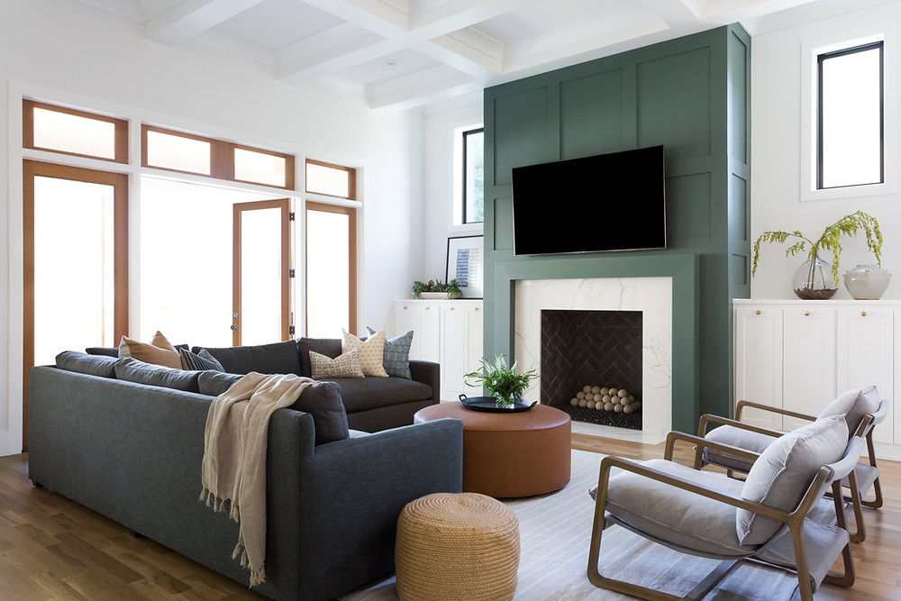 living room with charcoal sectional and green fireplace wall