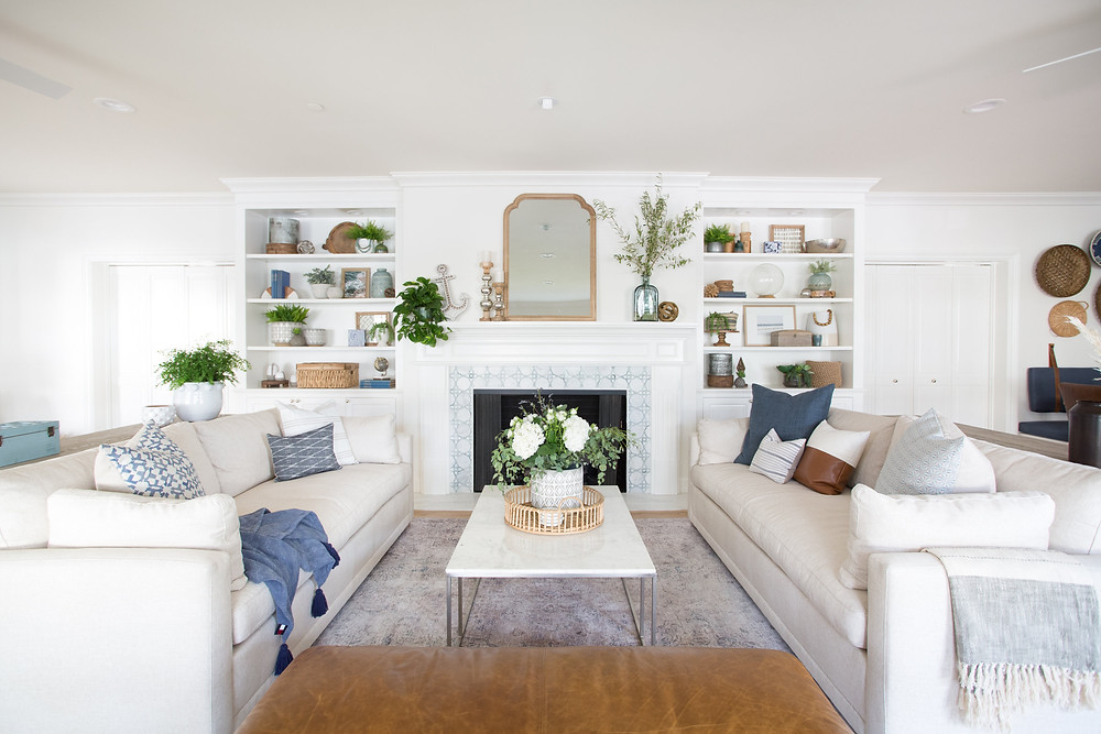 linen sofas with bookcases and blue tile fireplace