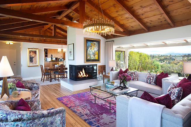 This gorgeous ranch style home sits perched atop a bluff in North San Diego, giving it breathtaking views of both ocean and sweeping hills and valleys. The living room was an often-used lounging area but needed a refresh for functionality. A lack of lighting made reading and playing piano difficult for the homeowners past the morning hours. While the wood beam ceiling was lovely, there was no space between the interior ceiling and roofing to add lighting. With help from an electrician, we were able to find a creative solution. We integrated recessed LED lighting within the beams themselves for task lighting then hard-wired stylish (and functional) chandeliers in both the living and dining areas.   The homeowners are avid art collectors, with the fireplace being a prime spot for display. We gave the original exterior brick a makeover with plaster and new glass doors, creating a much better complement for their contemporary home. Inspired by their collection, we added an area rug that resembles an impressionist's palette. And with the newfound ability to read and enjoy the piano, we added new furnishings for all-day relaxation