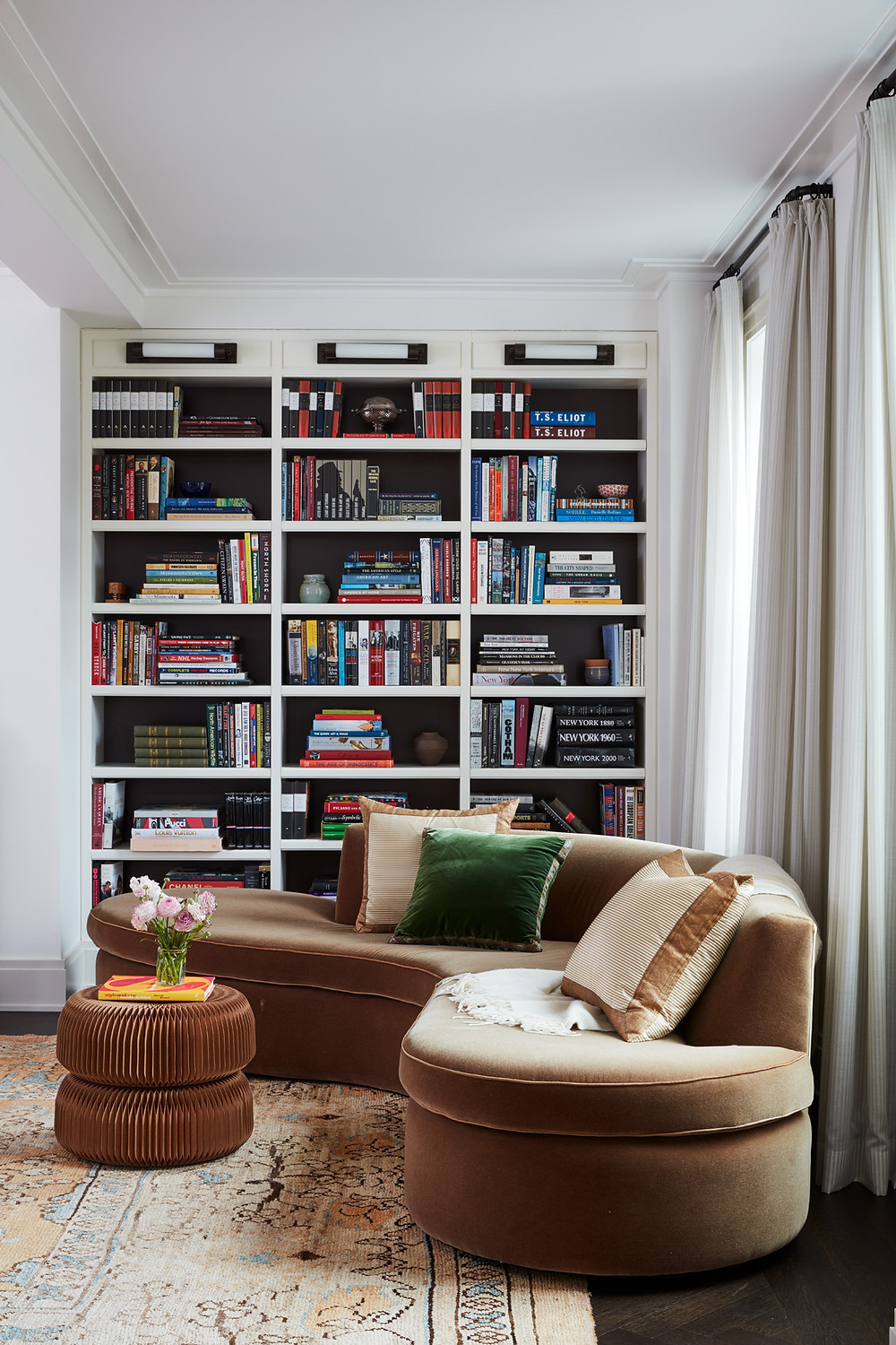 library with curved velvet sofa and vintage rug
