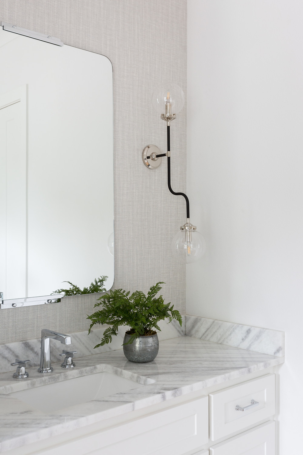 white vanity with grasscloth wallpaper