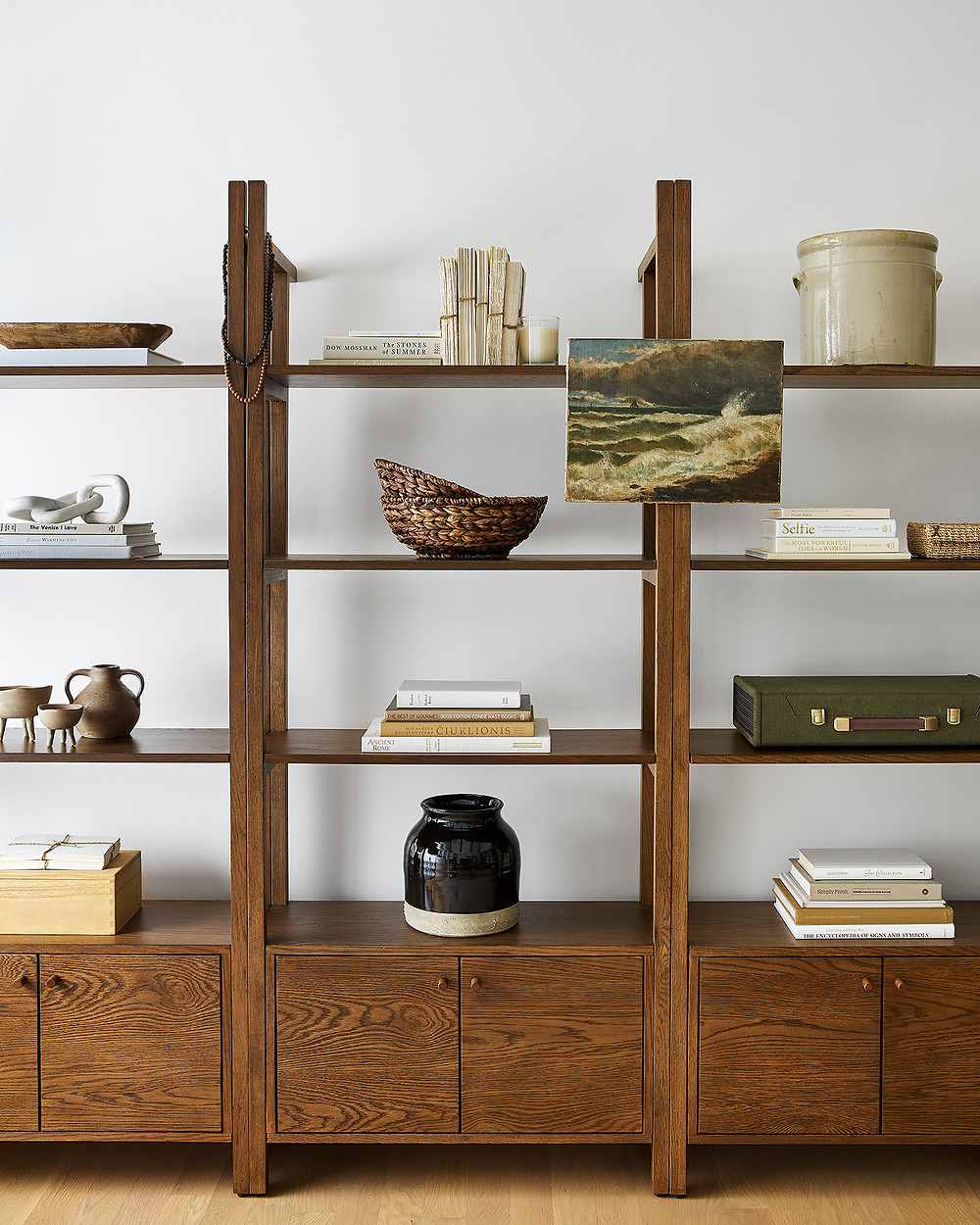 wood bookcases styled with pottery and baskets