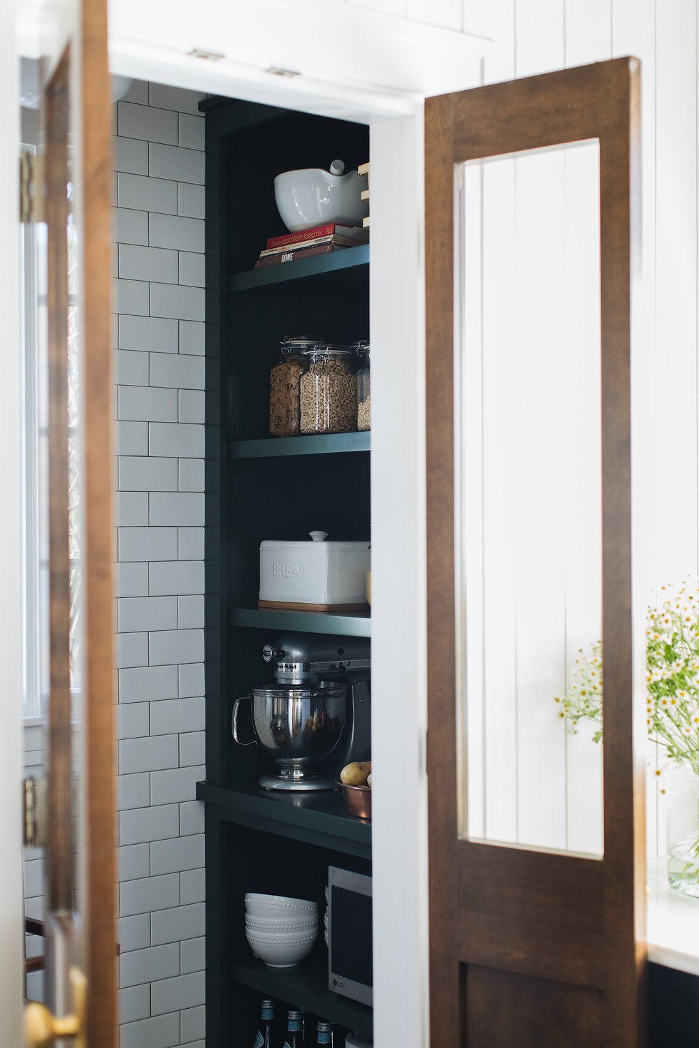 pantry with green shelves and subway tile