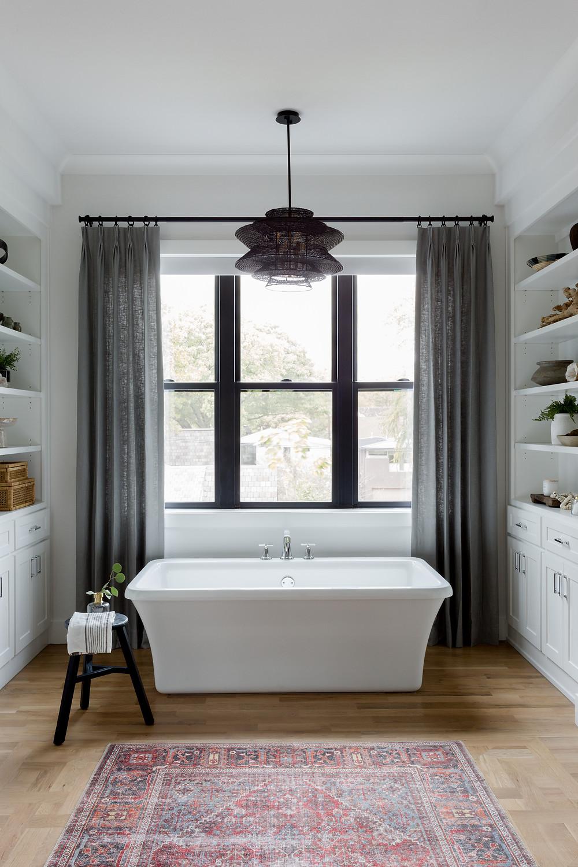 free-standing bathtub under window
