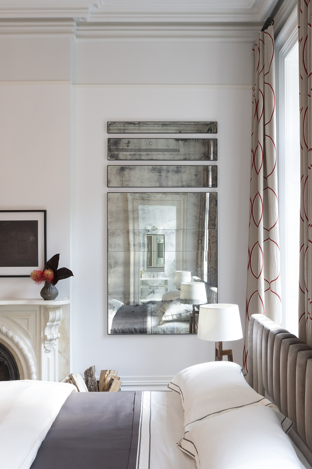 bedroom with upholstered headboard and antique mirror