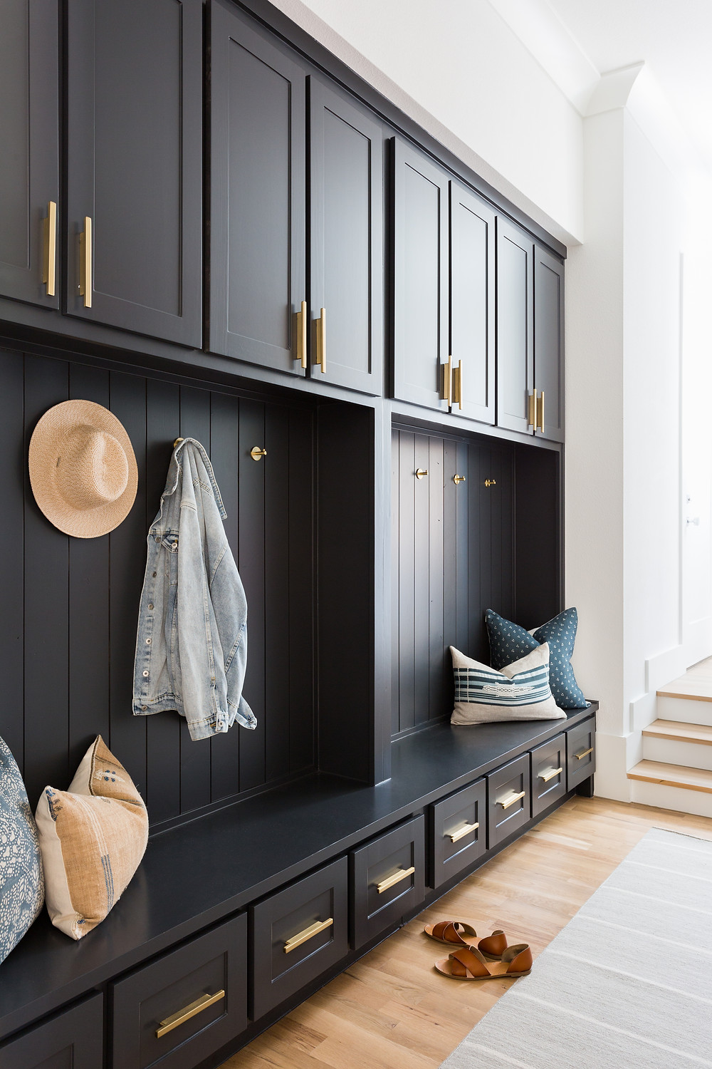 mudroom with dark cabinets and brass hardware