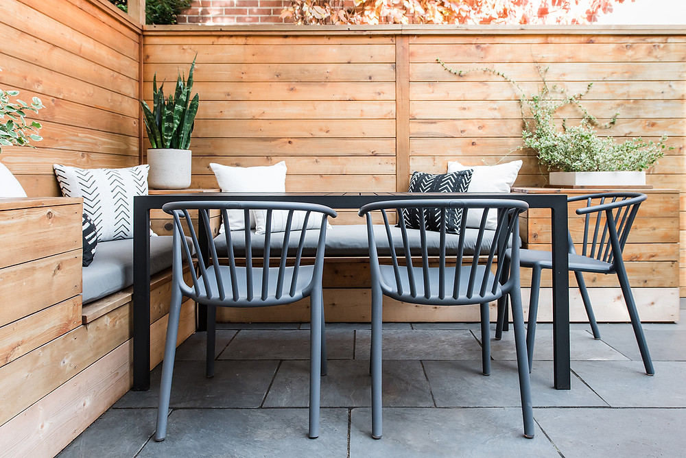 Sleek outdoor patio space in Washington, DC row house with built-in seating and storage, planters, pillows and blankets.