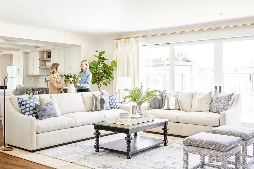 The difference between a full furnishing project and a remodel or new construction project. Warm and inviting living room design with linen sofas, an assortment of blue textured pillows, custom upholstered ottomans and pinch pleated window treatments  designed by Lexi Westergard Design.