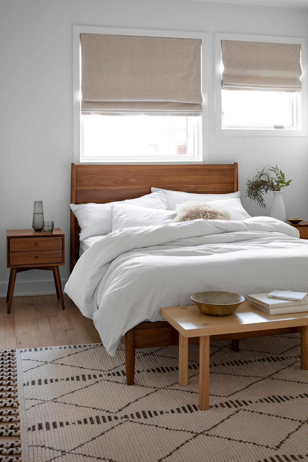 Calming neutral bedroom with geometric patterned rug and wooden bed frame.