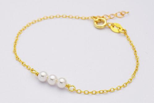 guld armbånd med små hvide perler