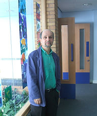 Peter Thabit Jones standing by a stained glass window in St. Thomas School, Swansea. The window is the work of the artist Catrin Jones. It features the poem 'Kilvey Hill' by Peter. This is etched on the glass and can be read from both sides of the artwork