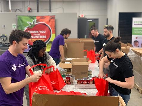 team volunteering ofs packing meals.JPG