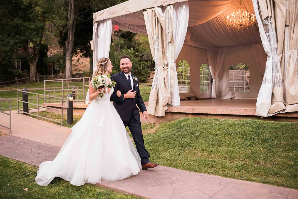 Bride and Groom Walk Past White Reception Tent at Wedgewood Boulder