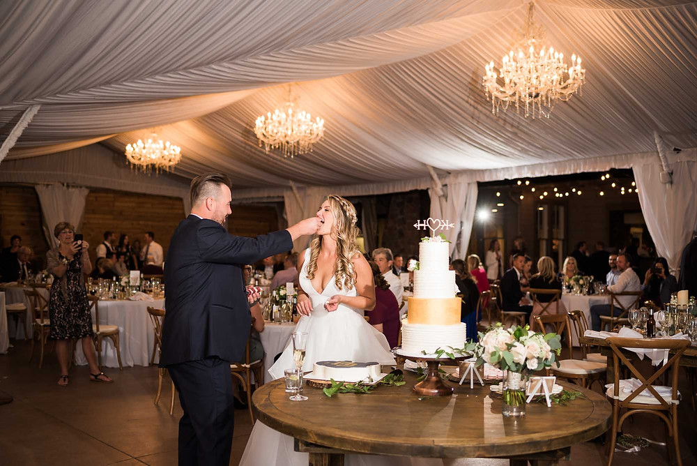 Groom Feeds Bride Wedding Cake in White Tent with Chandeliers