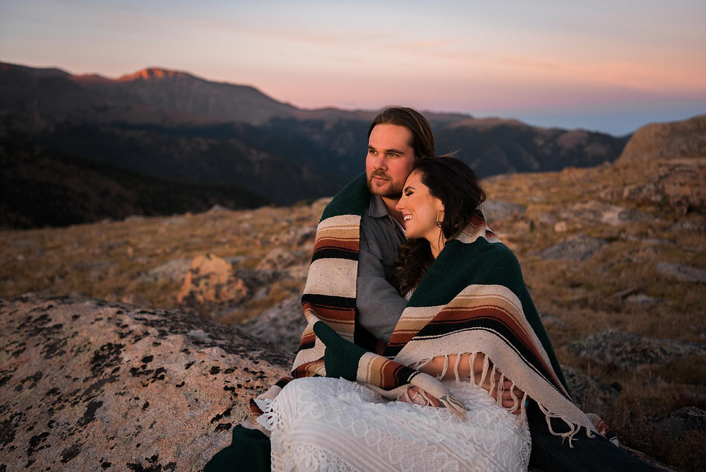 Couples Wrapped in Blanket for Warmth at High Altitude Engagement Session
