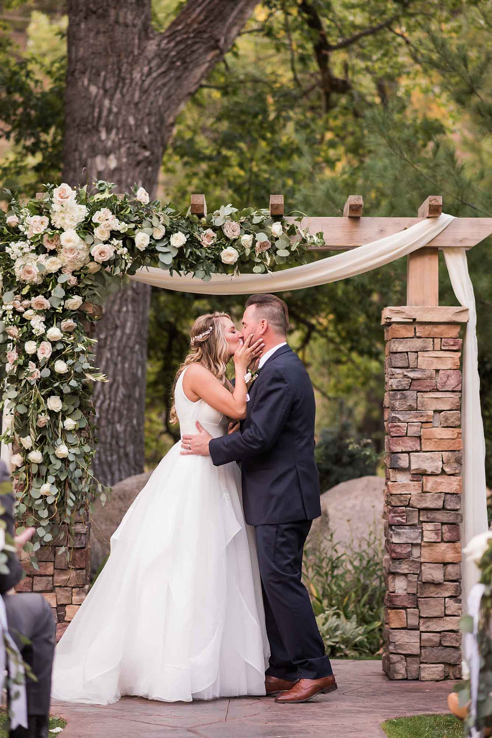 First Kiss at Wedgewood Boulder Under Painted Primrose Floral Arch