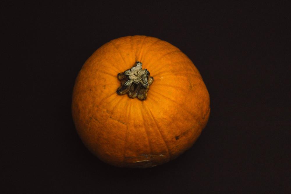A medium-sized orange pumpkin placed on black paper.