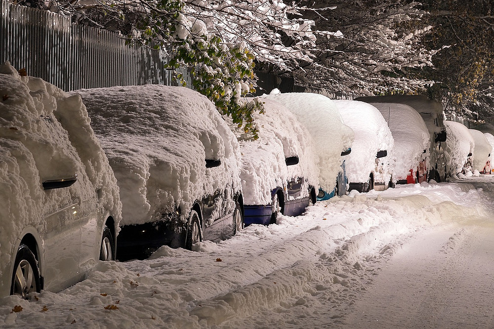 Cars on the street covered in snow.