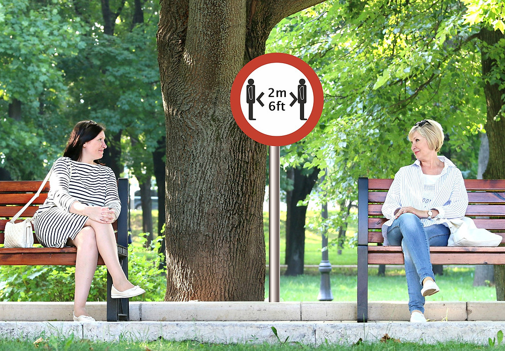 Two people sitting on different benches with a sign in between them that says 6 feet apart.