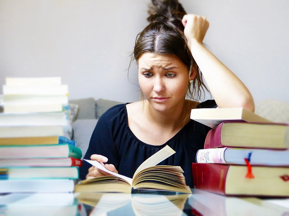 A woman looking stressed as she has many books around her.