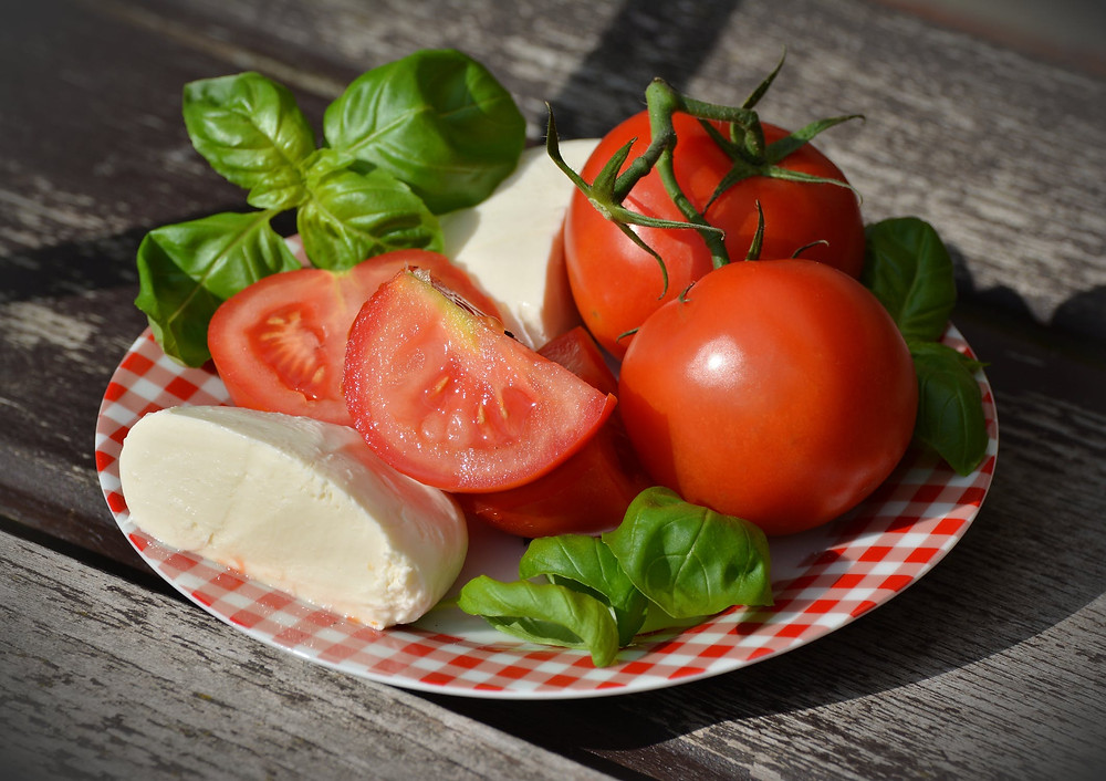 A plate of basil, mozzarella, and tomatoes.