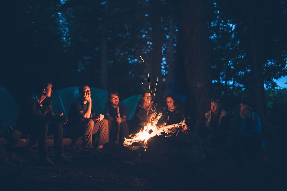 Friends sitting outside around a fire