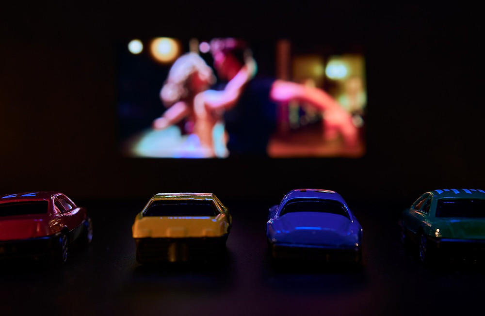 Toy cars lined up looking at a TV screen.