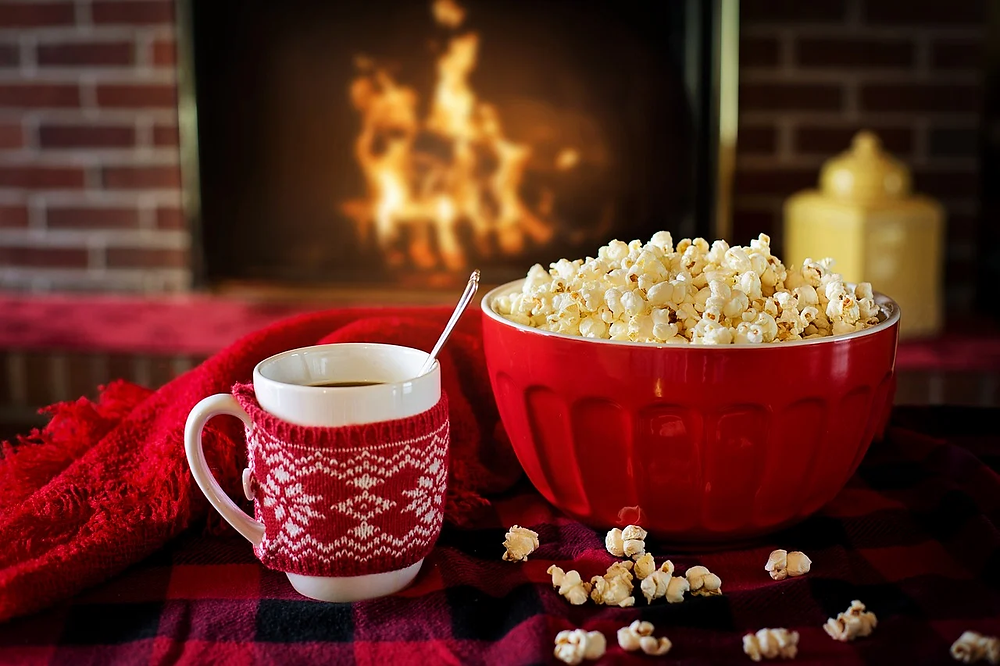 Popcorn and a hot drink near a fireplace.