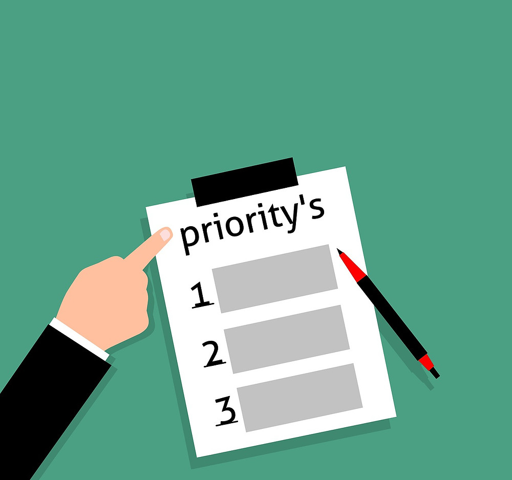 A person point holding a paper with a list of priorities.