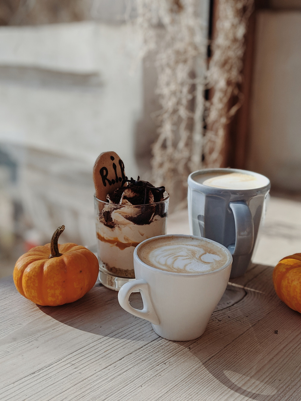 Cups of coffee with a Halloween-themed cookie desert, all placed beside two mini pumpkins.
