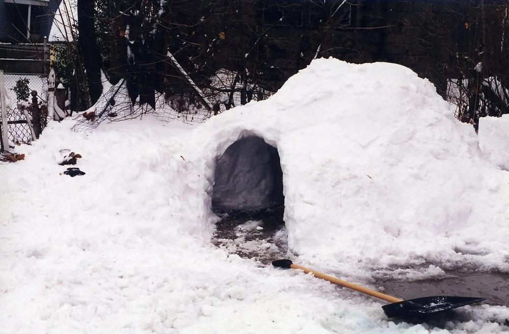 A snow fort built with a shovel in front of it.