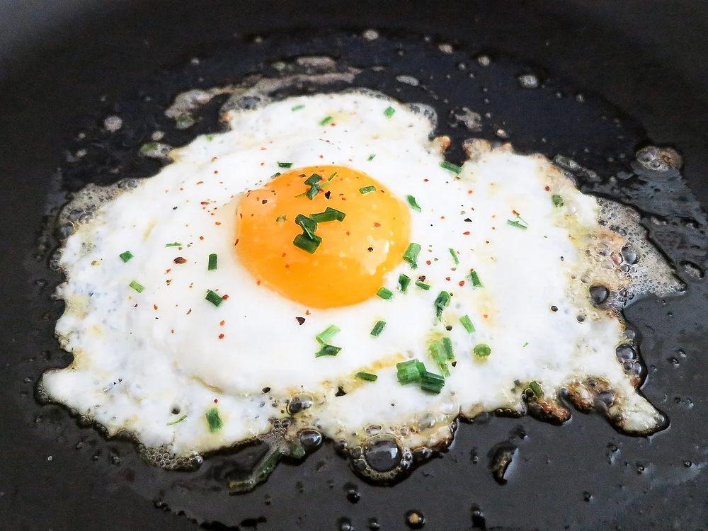 A sunny side up egg with chives on it.