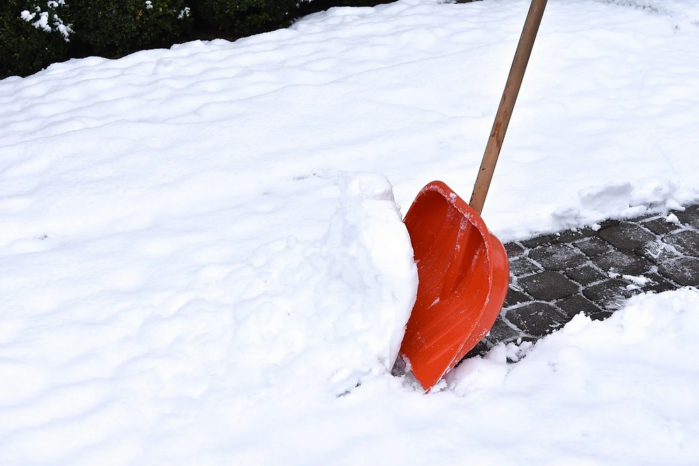 A red shovel pushing snow on a driveway.