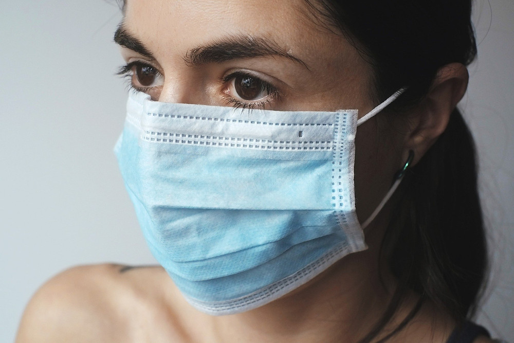 A girl wearing a blue surgical mask.