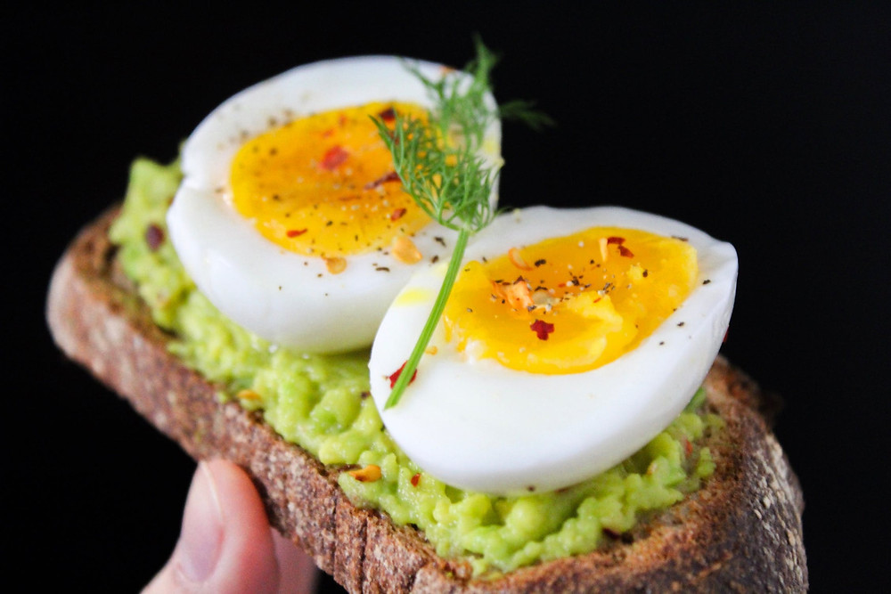 A person holding an avocado toast with a hard-boiled egg topped with sprinkled with black pepper and red peppers. .