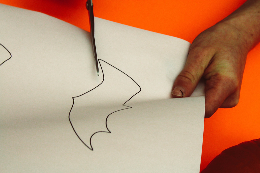 A Mohawk student cutting out a stencil of a batwing.
