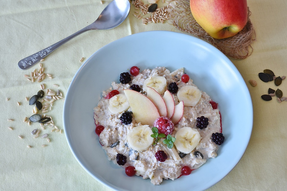A bowl of oatmeal with different fruit on top of it.