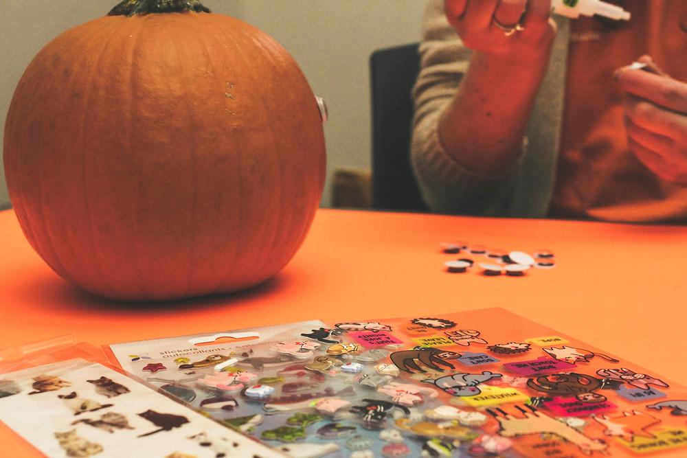 A Mohawk student decorating a pumpkin for Halloween.