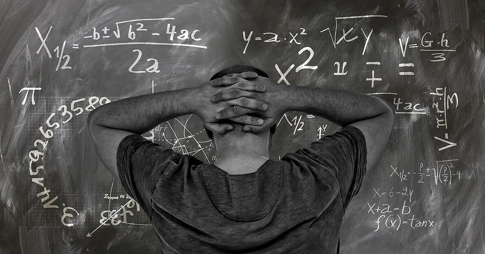 A man in front of a blackboard with math symbols all over it.