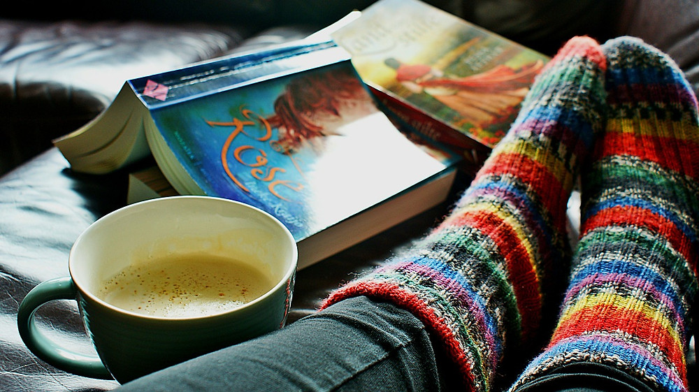 A persons feet next to a hot drink and books