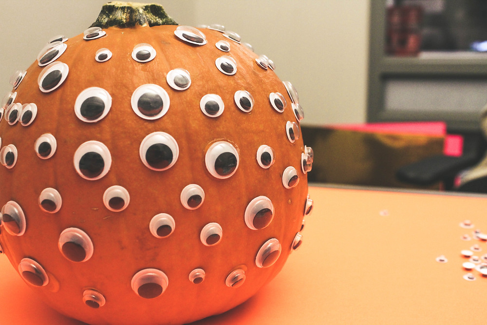 A pumpkin covered in googly eyes.