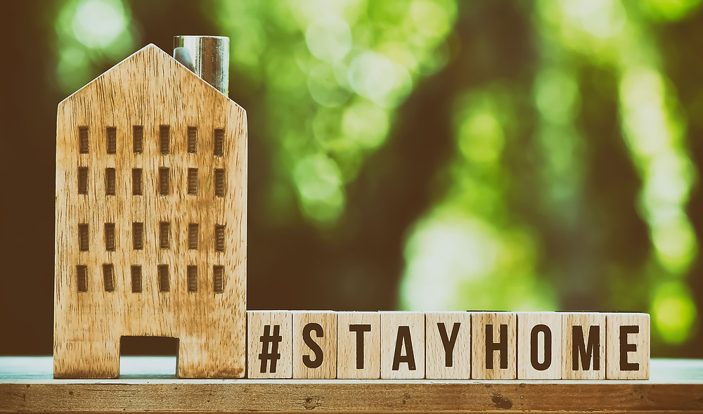 A small wooden building with wood letters next to it spelling out stayhome